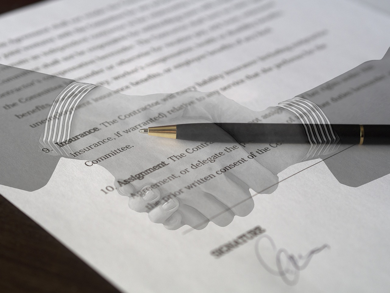 Handshake image superimposed over a signed contract